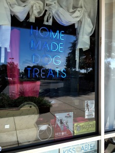 Neon lights reading HOME MADE DOG TREATS welcome customers who take a peek inside the storefront.